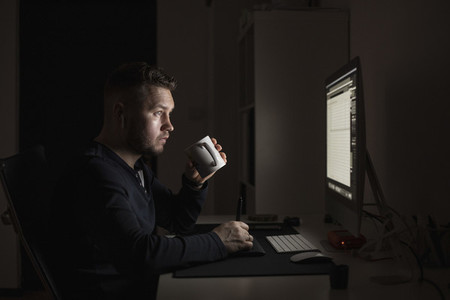 Man with coffee working late at computer in dark room