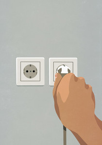 Hand plugging cord into electrical outlet