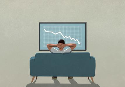 Man on sofa watching stock market decline on TV