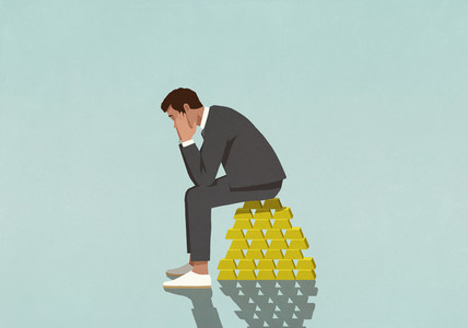Worried male investor sitting on stack of gold bars