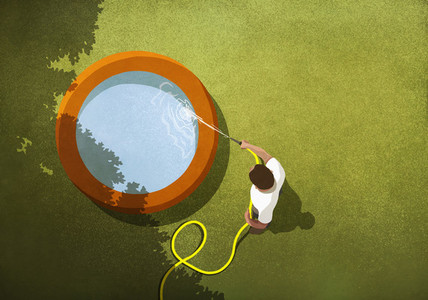 Man with hose filling wading pool in sunny backyard
