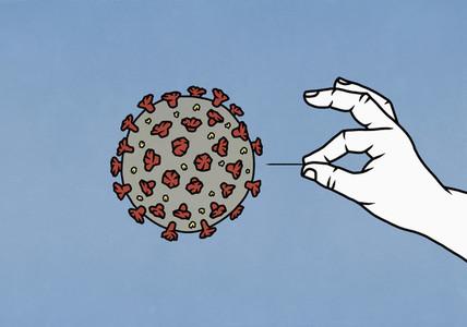 Hand with pin over COVID 19 coronavirus
