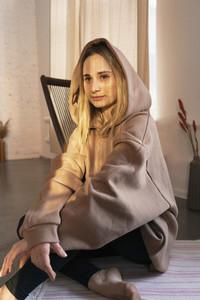 Portrait young blonde woman in hooded sweatshirt