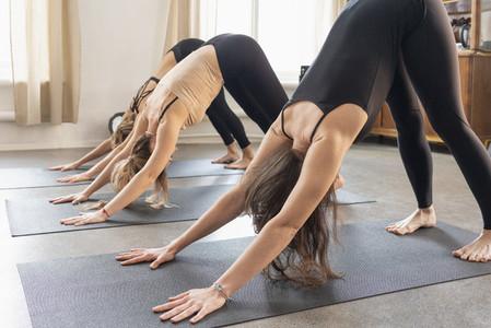 Young women practicing downward facing dog in yoga class