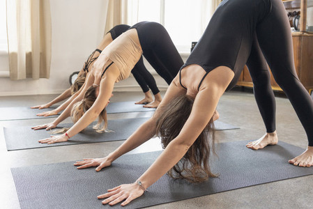 Young women practicing downward facing dog in yoga class
