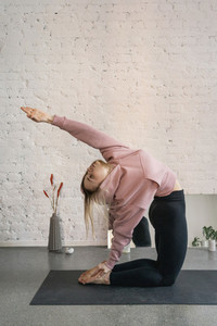 Young woman practicing camel pose backbend in yoga studio