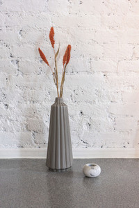 Simple modern vase with orange flowers against white brick wall