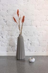 Simple modern vase with orange flowers against white brick wall