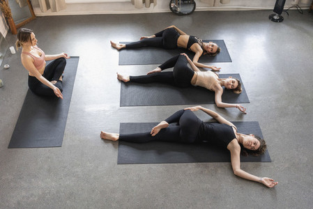 Yoga instructor and students practicing supine spinal twist in yoga class