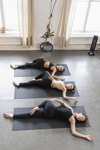 Young women practicing supine spinal twist in yoga class