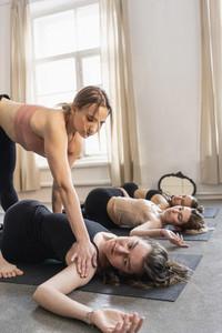 Yoga instructor adjusting student in supine spinal twist