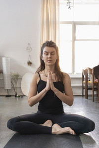 Serene young woman meditating on yoga mat