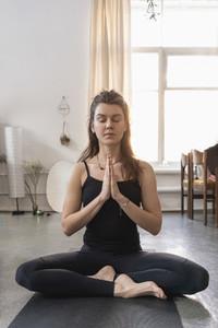 Serene young woman meditating on yoga mat