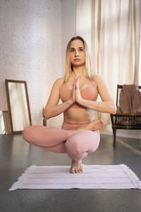 Young woman practicing yoga in yoga studio