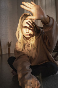 Portrait confident young woman in hooded sweatshirt blocking sunshine with hand