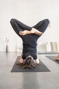 Flexible young woman practicing yoga in yoga studio