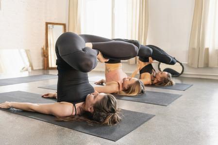 Young women practicing yoga in yoga studio