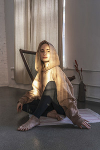 Portrait confident young woman in hooded sweatshirt in yoga studio