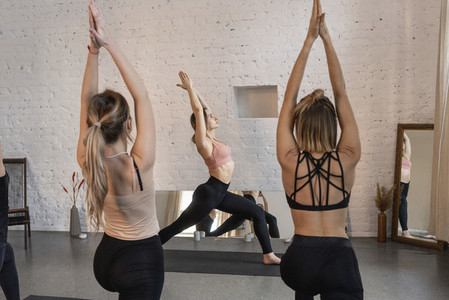 Young woman practicing warrior 1 pose in yoga class