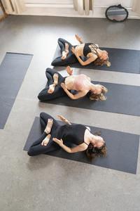 Young women practicing fish yoga pose in yoga studio