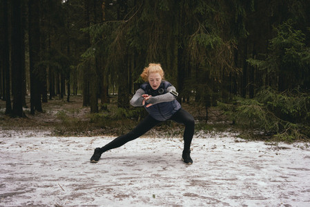 Athletic female runner stretching in snowy woods