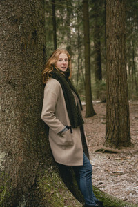 Portrait confident redhead woman in wool coat leaning against tree in woods