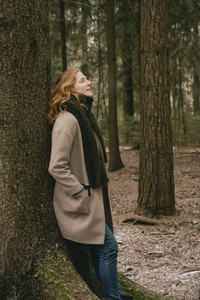 Serene redhead woman in wool coat and scarf leaning against tree in woods
