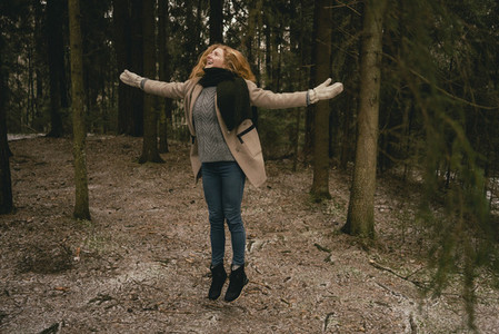 Carefree woman jumping for joy in woods