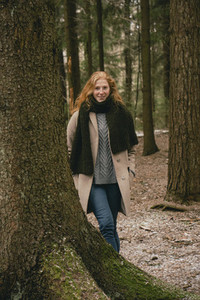 Portrait confident redhead woman in coat and scarf standing among trees in woods