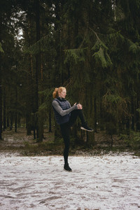 Female runner stretching legs in snowy woods