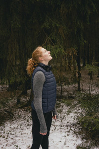 Serene redhead woman looking up in snowy woods