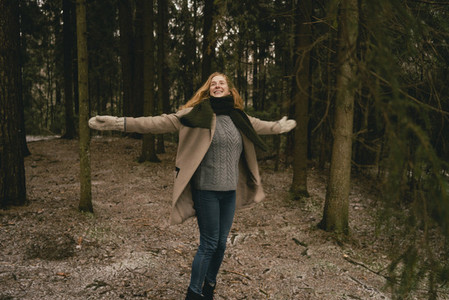 Exuberant carefree woman with arms outstretched in woods