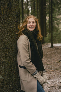 Portrait confident redhead woman in scarf and wool coat leaning against tree in woods