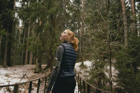 Curious female runner on footbridge in snowy woods