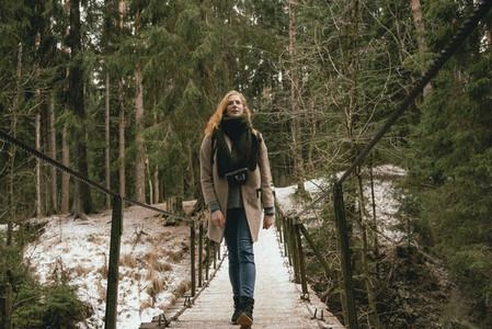 Woman in wool coat and scarf walking on footbridge in snowy woods
