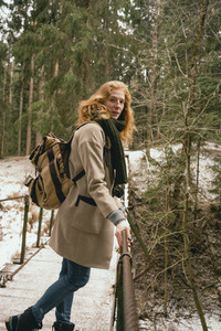 Portrait redhead woman with backpack on footbridge in snowy woods
