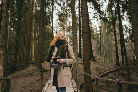 Serene redhead woman with camera on footbridge in woods