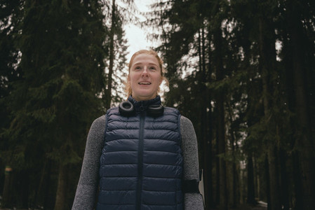 Portrait confident smiling female runner in woods