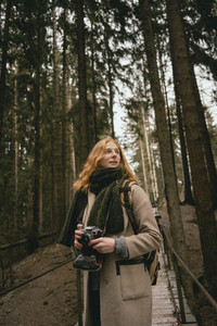 Redhead woman with camera on footbridge in woods