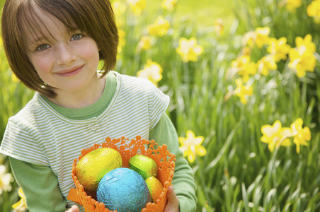 Portrait smiling girl with Easter egg candy in daffodil field