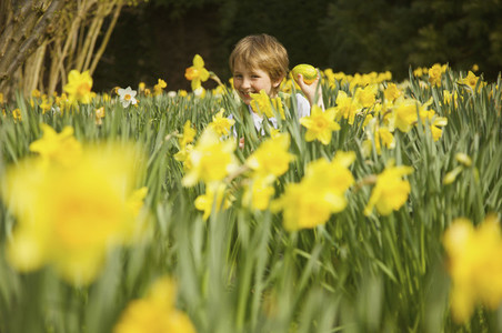 Portrait happy boy enjoying Easter egg hunt in field of yellow daffodils