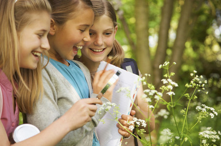Smiling girls with magnifying glass examining flowers on field trip