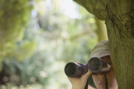 Curious girl with binoculars in woods