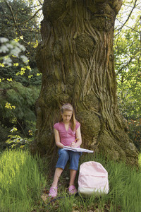Girl with notebook and backpack sitting below tree on field trip