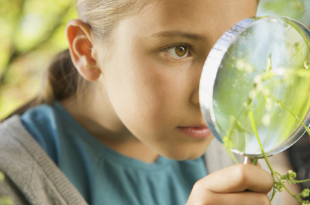 Close up curious girl with magnifying glass examining plant