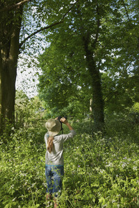 Curious girl with binoculars bird watching in sunny woods