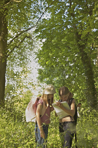 Girls with notebook on field trip in woods