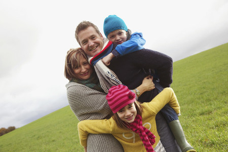 Portrait happy family hugging in grassy field