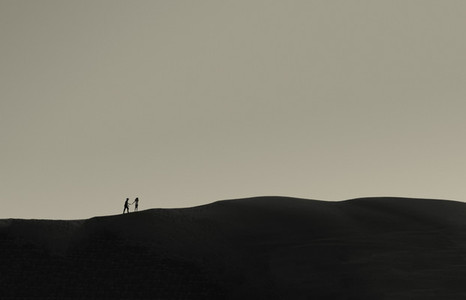 Silhouetted children walking over sand dunes