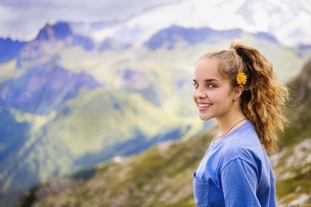 Portrait smiling girl with flower in hair hiking Dolomites Mountains